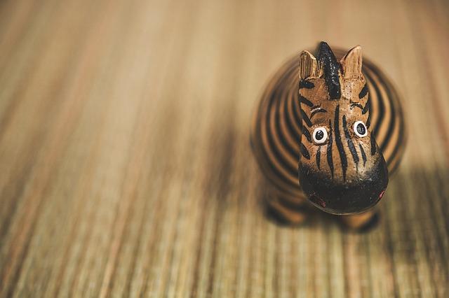 dřevěná zebra položena na koberci